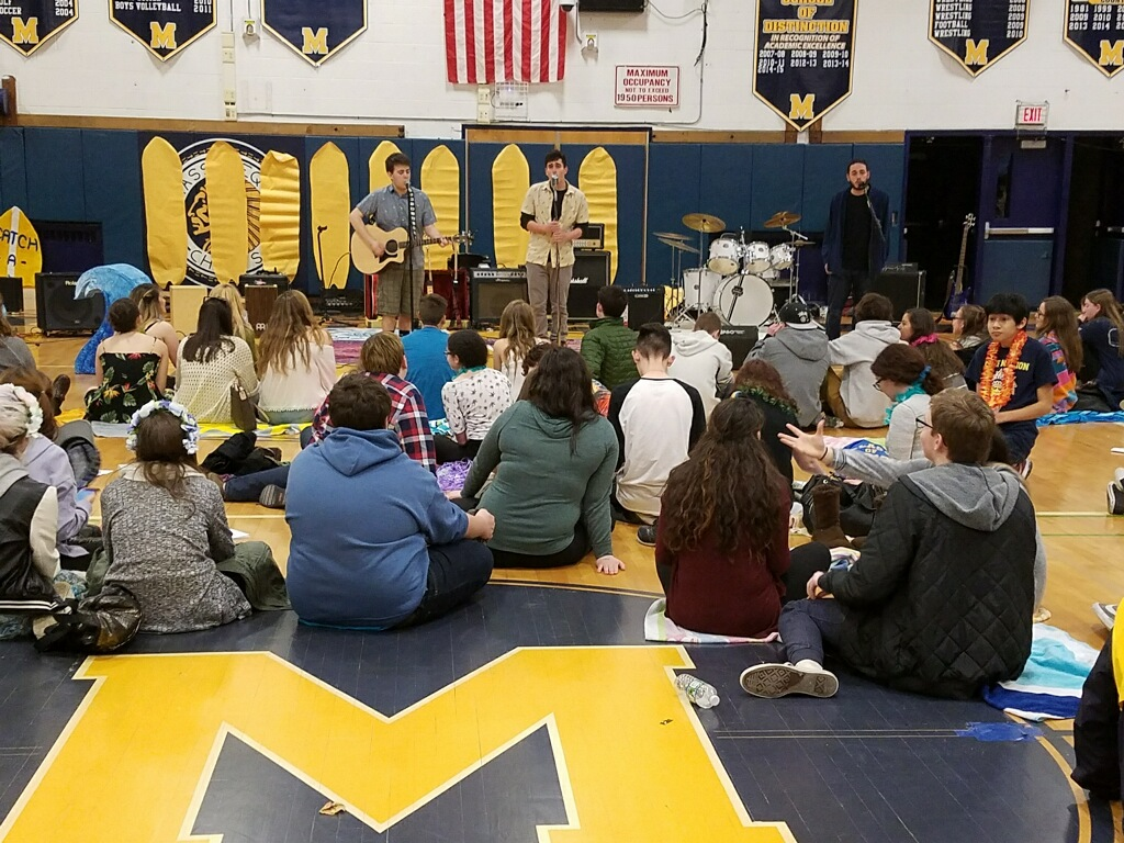An evening at the beach: Students sit on beach towels and enjoy the local tunes.